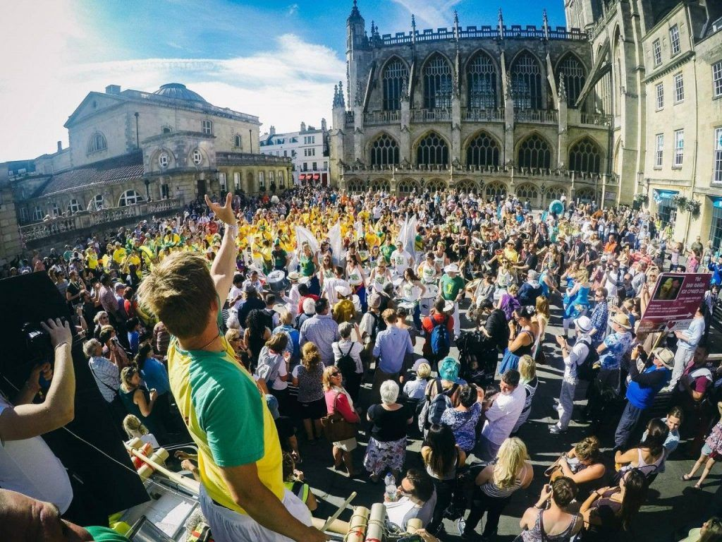 Crowds partying outside Bath Abbey during the Bath Carnival.